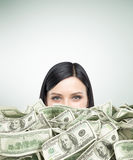 I am rich. Close up of girl's head with black hair piled up in cash. Concept of being too rich. Mock up Royalty Free Stock Image
