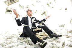 I am rich!. Happy young businessman in formalwear throwing money up while sitting near the case full of paper currency Stock Image