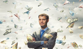 I am rich man. Businessman under rain of momey banknotes flying in the air stock image