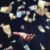 I am rich man. Businessman under rain of momey banknotes flying in the air stock images