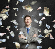 I am rich man. Businessman under rain of momey banknotes flying in the air royalty free stock images