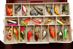 I richiami del pescatore in una vecchia scatola di attrezzatura Fotografie Stock