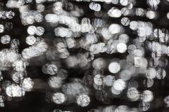 I riflessi leggeri dei chiarori rotondi di Glitttering in acqua sorgono in FO Immagine Stock