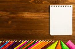 I rifornimenti di scuola disegnano a matita, rinchiudono, righello, triangolo sul BAC della lavagna Fotografia Stock