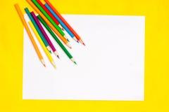 I rifornimenti di scuola e lo strato bianco su un fondo giallo luminoso, aspettano per la vostra progettazione Fotografie Stock Libere da Diritti