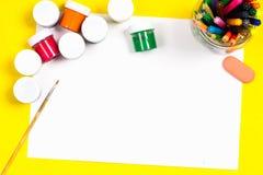 I rifornimenti di scuola e lo strato bianco su un fondo giallo luminoso, aspettano per la vostra progettazione Immagine Stock