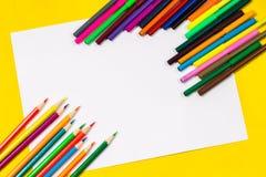 I rifornimenti di scuola e lo strato bianco su un fondo giallo luminoso, aspettano per la vostra progettazione Fotografia Stock Libera da Diritti