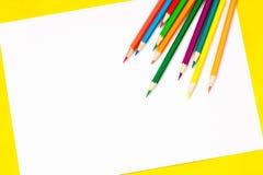 I rifornimenti di scuola e lo strato bianco su un fondo giallo luminoso, aspettano per la vostra progettazione Immagini Stock