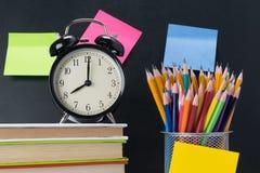 I rifornimenti e gli orologi di scuola sono sulla tavola fotografia stock
