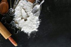 I rifornimenti e la taglierina bollenti del biscotto dell'albero di Natale rasentano il nero Fotografie Stock Libere da Diritti