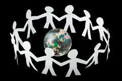 I ritagli di carta della gente cantano e ballano intorno al globo Immagine Stock