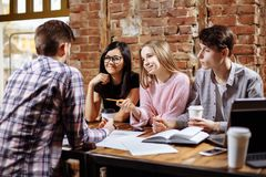 I riusciti giovani stanno utilizzando un computer portatile, caffè bevente, stanno parlando e sorridendo mentre lavoravano in caf Immagine Stock