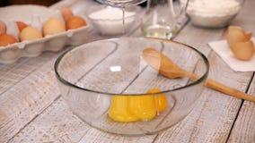 I rossi d'uovo di caduta movimento lento, preparano l'alimento casalingo nella cucina archivi video