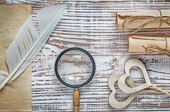 I rotoli d'annata della carta dello strato plume la lente di legno dei cuori su legno Fotografie Stock Libere da Diritti
