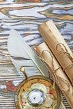 I rotoli di carta d'annata plume la candela del candeliere sul bordo di legno immagini stock