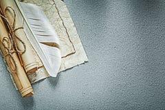 I rotoli di carta d'annata plume sulla vista superiore del fondo grigio immagini stock