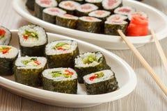 I rotoli di sushi con il nori, il riso, pezzi di avocado, il cetriolo, rosso sono Fotografia Stock