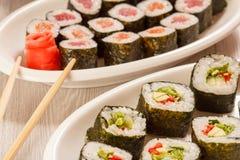 I rotoli di sushi con il nori, il riso, pezzi di avocado, il cetriolo, rosso sono Immagine Stock Libera da Diritti