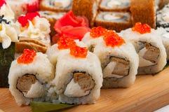 I rotoli di sushi hanno ordinato su un concetto del bordo di legno: consegna Immagini Stock Libere da Diritti