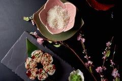 I rotoli di sushi sono servito sotto forma del fiore con wasabi Piatto con riso vicino su una tavola Vista superiore fotografie stock libere da diritti