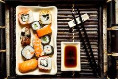 I rotoli ed il piatto dei sushi con la salsa di soia Fotografie Stock