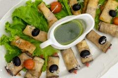 I rotoli fritti della melanzana con le olive nere penetranti con gli spiedi si trovano sulle foglie della lattuga Salsa verde in  immagini stock