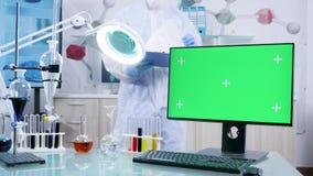I säkert laboratorium ett skrivbord med den gröna skärmPCbildskärmen arkivfilmer