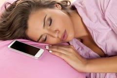 I säng med hennes telefon royaltyfri foto