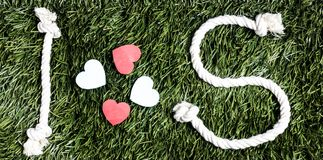 I and S letters and three paper heart cut outs on grass. I and S letters and three paper heart cut outs on grass Stock Photography