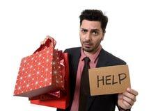 I sacchetti della spesa della tenuta dell'uomo d'affari ed il segno di aiuto si sono preoccupati e l'espressione del fronte di sf Immagini Stock