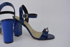 I sandali delle donne blu per le donne dalla pelle verniciata genuina con il sottopiede dell'oro sugli alti grandi e talloni spes fotografia stock libera da diritti
