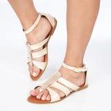 I sandali di cuoio beige con oro hanno applicato sui piedi il mujere su fondo bianco fotografie stock libere da diritti