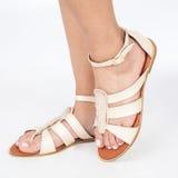 I sandali di cuoio beige con oro hanno applicato sui piedi il mujere su fondo bianco fotografia stock libera da diritti