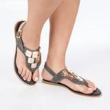 I sandali di cuoio grigi con oro hanno applicato sui piedi il mujere su fondo bianco fotografie stock