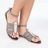 I sandali di cuoio grigi con oro hanno applicato sui piedi il mujere su fondo bianco fotografia stock
