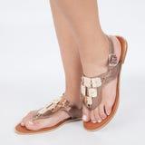 I sandali di cuoio marroni luminosi con oro hanno applicato sui piedi il mujere su fondo bianco immagini stock libere da diritti