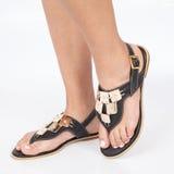 I sandali di cuoio neri con oro hanno applicato sui piedi il mujere su fondo bianco immagini stock libere da diritti