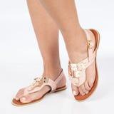 I sandali di cuoio rosa con oro hanno applicato sui piedi il mujere su fondo bianco immagini stock
