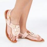 I sandali di cuoio rosa con oro hanno applicato sui piedi il mujere su fondo bianco fotografia stock libera da diritti
