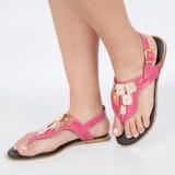 I sandali di cuoio rosa scuri con oro hanno applicato sui piedi il mujere su fondo bianco fotografia stock libera da diritti