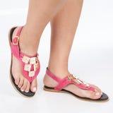 I sandali di cuoio rosa scuri con oro hanno applicato sui piedi il mujere su fondo bianco immagini stock