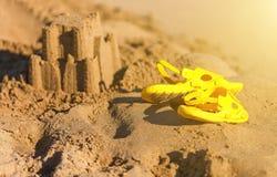 I sandali ed il castello di giallo del ` s del bambino sta risiedendo nella sabbia Viaggio, festa e vacanza di concetto Immagini Stock