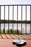I sandali sul patio di un lago fronteggiano l'appartamento Immagini Stock
