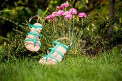 I sandali verdi si trovano sull'erba, scarpe comode delle signore Fotografia Stock