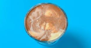 I sapori di vavanilla e del cioccolato le palle del gelato che si fondono in un timelapse 4K della tazza video d archivio