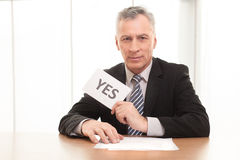 I say yes!. Confident senior man in formalwear sitting at the table and holding yes sign Stock Photo
