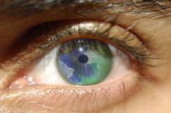 I see the world in your eyes. Conceptual image of the globe in the iris of a person Royalty Free Stock Photography