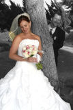 I see you. Bride poses for photo while groom looks on Royalty Free Stock Image