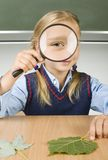 I see you. Little girl with magnifying glass in hand. Sitting at desk in front of blackboard. Magnifying her's eye. Looking at camera. Front view Stock Photos