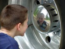 I See You. A boy and his dog reflected in an International Loanstar 1800 dump truck wheel hubcap Stock Photos